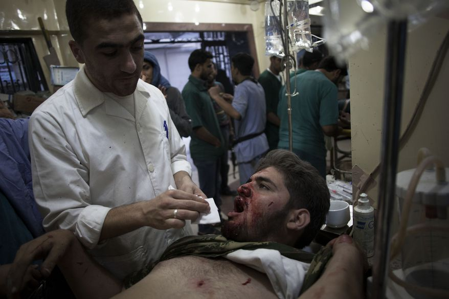 **FILE** Syrian doctor treats a wounded Free Syrian Army fighter on Oct. 13, 2012, at Dar al-Shifa hospital in Aleppo, Syria. (Associated Press)