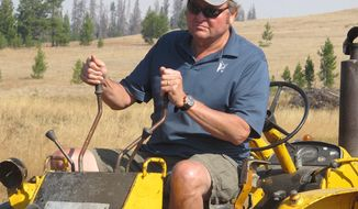 Montana Gov. Brian Schweitzer operates a backhoe on Wednesday, Sept. 19, 2012, as he clears a stream under a bridge he built on his ranch in Marysville, Mont., about 45 miles from the capital, Helena. (AP photo/Matt Gouras)