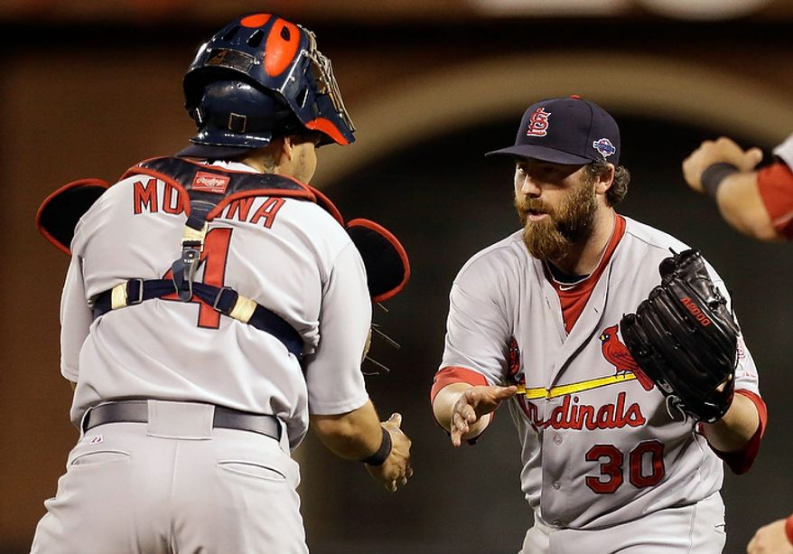 St. Louis Cardinals relief pitcher Jason Motte (30) celebrates with catcher Yadier Molina after winning Game 1 of baseball's National League championship series 6-4 against the San Francisco Giants Sunday, Oct. 14, 2012, in San Francisco. (AP Photo/Ben Margot)