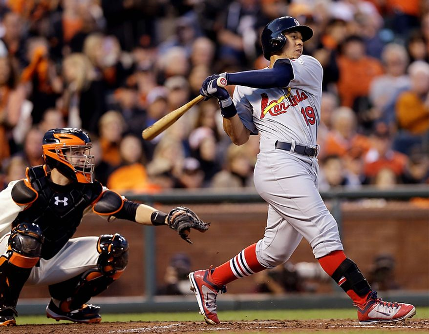 San Francisco Giants catcher Buster Posey watches as St. Louis Cardinals' Jon Jay hits an RBI single during the fourth inning of Game 1 of baseball's National League championship series Sunday, Oct. 14, 2012, in San Francisco. (AP Photo/David J. Phillip)