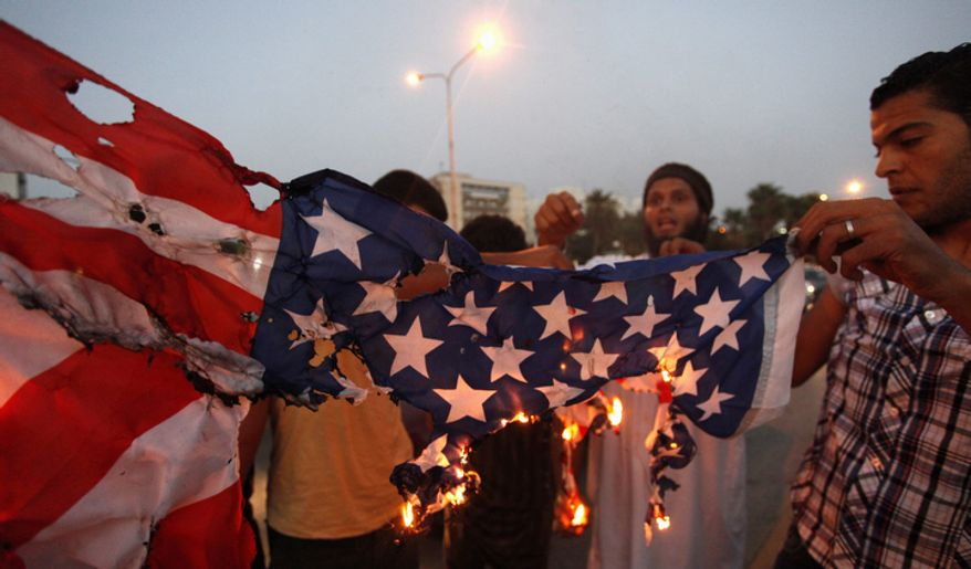 Libyan followers of the Ansar al-Shariah Brigades burn the U.S. flag during a protest in front of the Tibesti Hotel in Benghazi, Libya, on Friday, Sept. 14, 2012. Small teams of U.S. special operations forces arrived at American embassies throughout North Africa to set up a new counterterrorist network months before militants killed the U.S. ambassador in Libya at the U.S. Consulate in Benghazi on Sept. 11, but officials say the network was too new to stop that attack. (AP Photo/Mohammad Hannon)