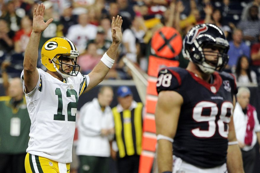 Green Bay Packers quarterback Aaron Rodgers (12) celebrates a touchdown as Houston Texans outside linebacker Connor Barwin (98) walks away in the fourth quarter of an NFL football game, Sunday, Oct. 14, 2012, in Houston. The Packers won 42-24. (AP Photo/Dave Einsel)