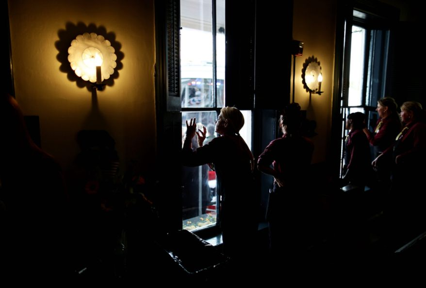 Staff members at The Golden Lamb Inn and Restaurant in Lebanon, Ohio, watch as Republican presidential candidate Mitt Romney campaigns on Oct. 13, 2012. (Associated Press)