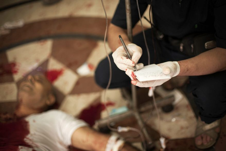 A Syrian doctor notes the name of a severely wounded man at Dar al-Shifa Hospital in Aleppo, Syria, on Thursday, Oct. 11, 2012. (AP Photo/Manu Brabo)