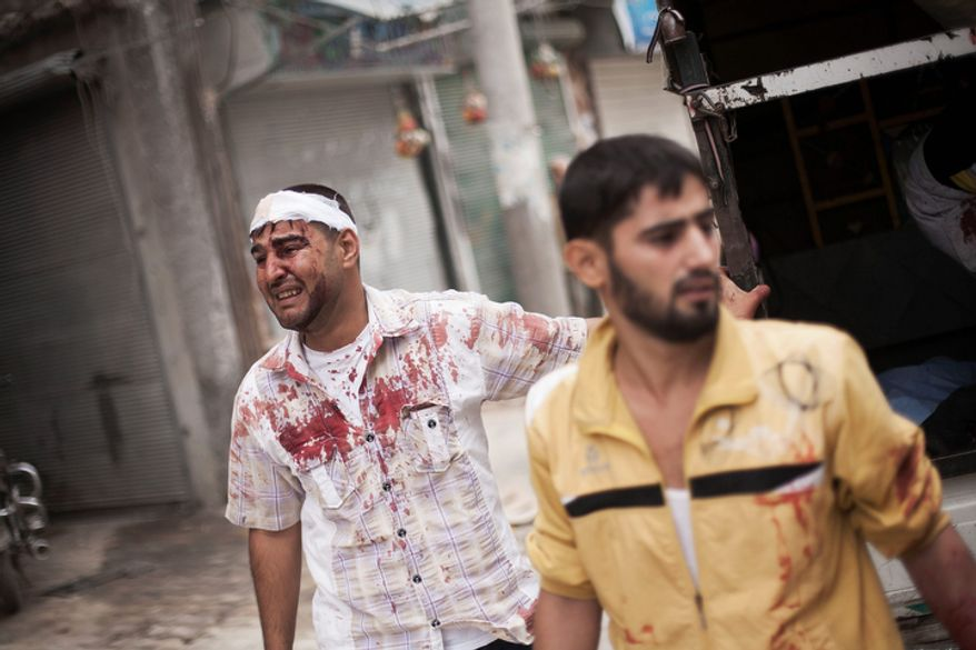 A Syrian man, wounded by Syrian army shelling, cries while the bodies of his relatives lie on the street near Dar al-Shifa Hospital in Aleppo, Syria, on Thursday, Oct. 11, 2012. (AP Photo/Manu Brabo)