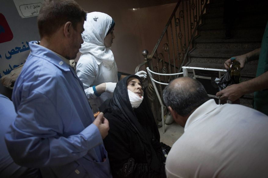 Doctors, nurses and volunteers help a wounded woman at Dar al-Shifa Hospital in Aleppo, Syria, on Thursday, Oct. 11, 2012. (AP Photo/Manu Brabo)