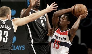 Brooklyn Nets forward Mirza Teletovic (33) and center Andray Blatche (0) defend against Washington Wizards' Jordan Crawford during the first half of their NBA preseason game at Barclays Center, Monday, Oct. 15, 2012, in New York. (AP Photo/Kathy Willens)