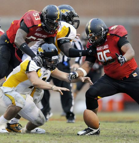 Towson quarterback Peter Athens, center, fumbles the ball as Maryland players, left to right, David Mackell, Lorne Goree and A.J. Francis, look to recover during the second half of an NCAA college football game, Saturday, Oct. 1, 2011, in College Park. Md. Maryland recovered the fumble and won the game 28-3. (AP Photo/Gail Burton)