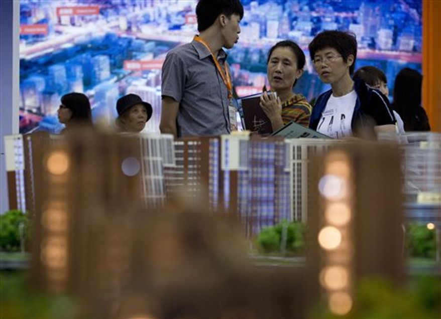 ** FILE ** In this Sept. 21, 2012 photo, people view housing models on display during the China Property and Investment Show in Beijing, China. People in China are increasingly worried about corruption, inequality and food safety, according to a survey that also found that about half of Chinese like American ideas about democracy. (AP Photo/Andy Wong, File)