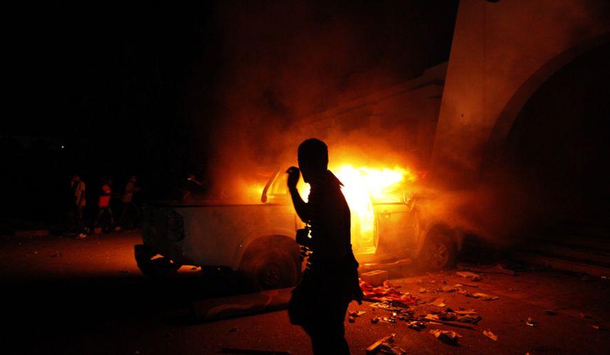 A Libyan civilian watches cars burn in Benghazi, Libya, in 2012. (Associated Press)