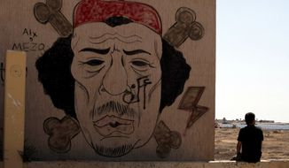**FILE** A Libyan man sits Sept. 20, 2012, near a mural of Moammar Gadhafi in Benghazi, Libya. (Associated Press)