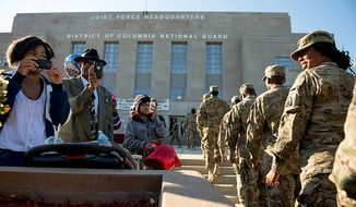 Family and friends take photos with their phones as 70 D.C. Army National Guard soldiers with the 273rd military police arrive in formation for their welcome home ceremony after returning from Bagram Air Base after 10 months, Afghanistan, Washington, D.C., Tuesday, October 16, 2012. (Andrew Harnik/The Washington Times)