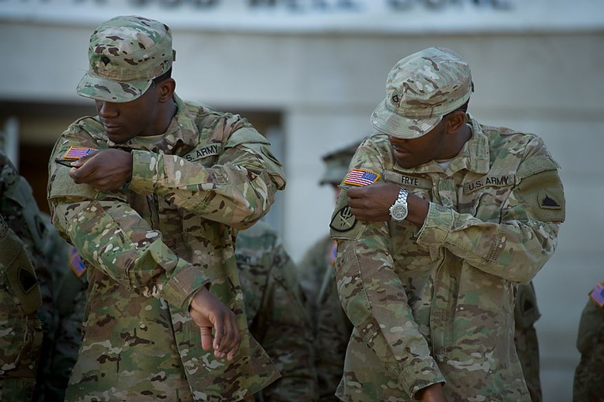 Spc. Jonathan Martin, left, and Pfc. Michael Frye, right, are awarded an  Joint Special Operations Command patch for deploying overseas at a welcome home ceremony held in front of the D.C. Armory for the 70 D.C. Army National Guard soldiers with the 273rd military police company returning from Bagram Air Base, Afghanistan after 10 months, Washington, D.C., Tuesday, October 16, 2012. (Andrew Harnik/The Washington Times)