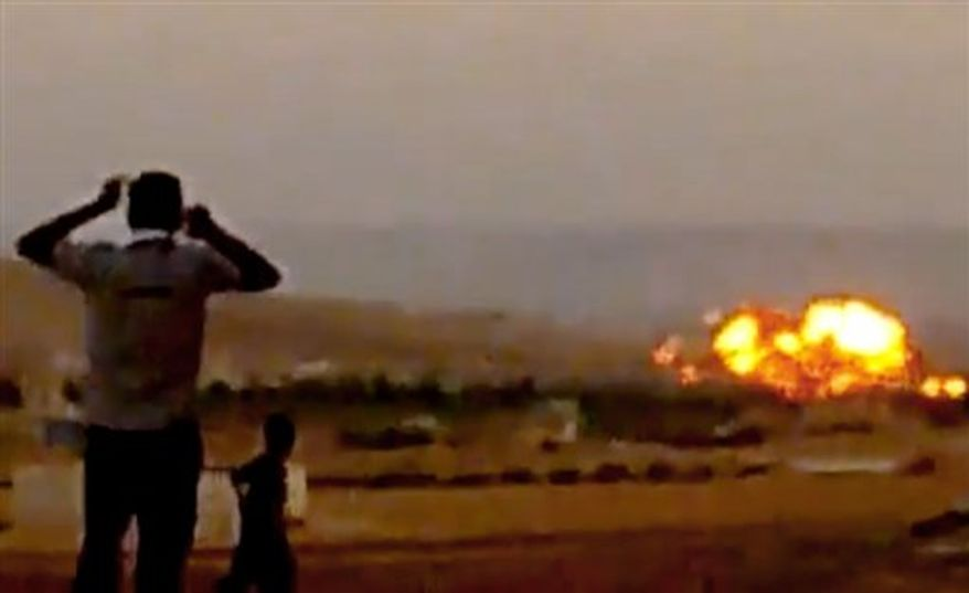 In this image taken from video obtained from the Ugarit News, which has been authenticated based on its contents and other AP reporting on Tuesday, Oct. 16, 2012, Syrians react after a government warplane was shot down in Aleppo, Syria, on Monday, Oct. 15, 2012. (AP Photo/Ugarit News via AP video)