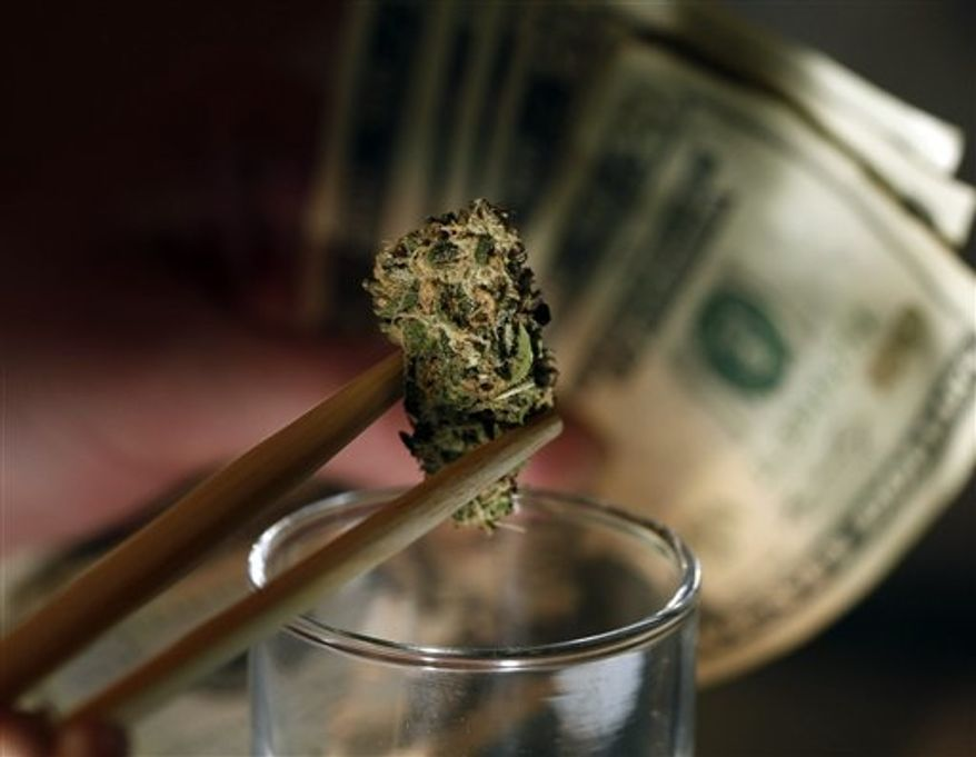 ** FILE ** A caregiver picks out a marijuana bud for a patient at a marijuana dispensary in Denver on Tuesday, Sept. 18, 2012. (AP Photo/Ed Andrieski)