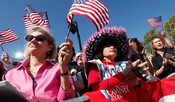 Supporters of Republican vice presidential candidate, Rep. Paul Ryan, R-Wis., wave flags  during a rally at Automated Conveyor Systems in Lynchburg, Va., Tuesday, Oct. 16, 2012.  (AP Photo/Steve Helber)