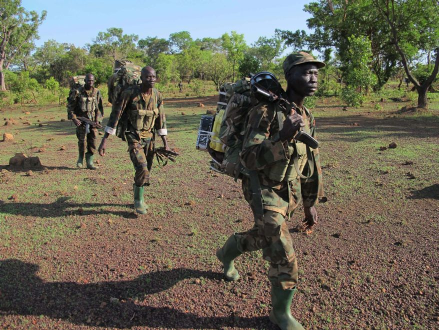 **FILE** Ugandan soldiers hunting for fugitive warlord Joseph Kony deep in the Central African Republic jungle patrol the area on April 19, 2012. (Associated Press)