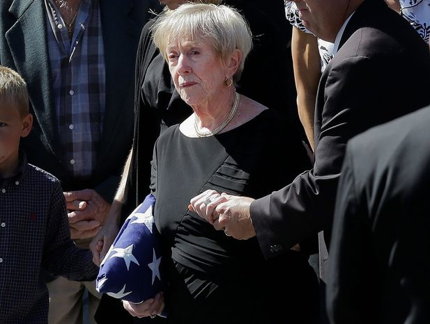 Barbara Doherty, mother of slain former Navy SEAL Glen Doherty, is escorted from his funeral. He was killed in Benghazi, Libya. Mitt Romney stopped telling a story about his encounter with the former SEAL after Mrs. Doherty objected. (Associated Press)