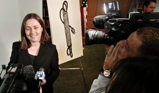 """Barbara Bertozzi, the widow of American art dealer Leo Castelli, stands next to the Roy Lichtenstein painting, """"Electric Cord,"""" which had been missing for 42 years, after it was returned to her by Preet Bharara, U.S. Attorney for the Southern District of New York, at a news conference on Tuesday, Oct. 16, 2012 in New York. (AP Photo/Bebeto Matthews)"""