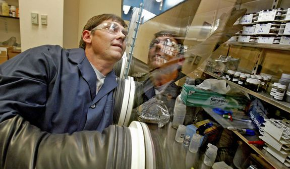 In this Aug. 9, 2007, photo, development technician Ronnie Wilkins reaches for some development powder stored in a glove box used in lithium car batteries A123 Systems Inc. headquarters in Watertown, Mass. After years of struggling with weak sales and mounting losses, the electric-car battery maker filed for bankruptcy protection and reached a deal to sell its automotive assets Tuesday, Oct. 16, 2012. (AP Photo/Boston Herald, David Goldman)