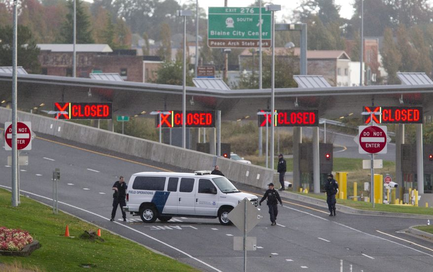 U.S. border agents work at the closed border crossing between Surrey, British Columbia, and Blaine, Wash., on  Tuesday, Oct. 16, 2012, after a Canadian border officer was shot in the neck by a man trying to enter Canada in a van with Washington state plates. (AP Photo/The Canadian Press, Jonathan Hayward)