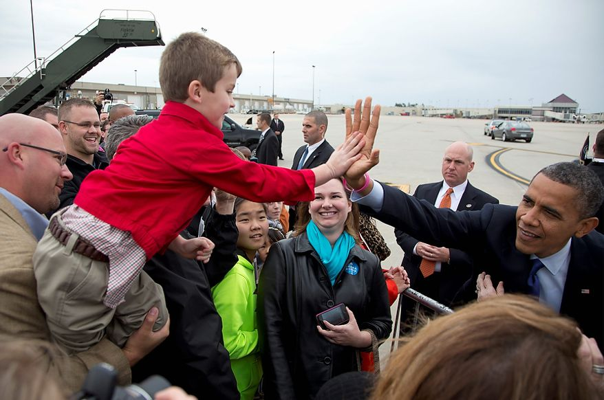 President Obama high-fives a boy Oct. 17, 2012, as he greets supporters on the tarmac upon arriving at Eastern Iowa Airport in Cedar Rapids, Iowa, for a campaign stop. The president sports a pink bracelet in honor of October being National Breast Cancer Awareness Month. (Associated Press)
