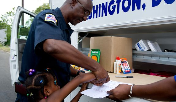 Officer Tony Nwani [cq] of the Mobile Crime Unit fingerprints Shirley Stewart, 6, of Washington, D.C., during National Night Out on Tuesday, Aug. 2, 2011. Metropolitan Police Department officers around the District reach out to the community on National Night Out in an effort to improve police-community relations. (Barbara L. Salisbury/The Washington Times)