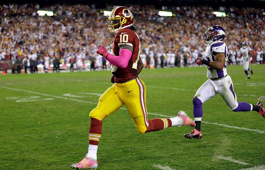 Washington Redskins quarterback Robert Griffin III (10) runs away from Minnesota Vikings safety Jamarca Sanford (33) for a 76-yard touchdown during the second half of an NFL football game, Sunday, Oct. 14, 2012, in Landover, Md. (AP Photo/Pablo Martinez Monsivais)