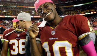 Washington Redskins quarterback Robert Griffin III (10) pulls tape off his chin after an NFL football game against the Minnesota Vikings on Sunday, Oct. 14, 2012, in Landover, Md. The Redskins won 38-26. (AP Photo/Pablo Martinez Monsivais)
