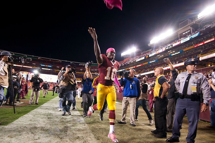 Washington Redskins quarterback Robert Griffin III (10) runs into the tunnel after winning 38 to 26 against the Minnesota Vikings, Landover, Md., Sunday, Oct. 14, 2012.  (Craig Bisacre/The Washington Times)