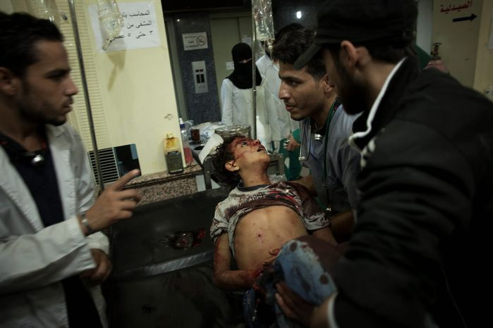 **FILE** Syrian medics hold a dead child at the Dar al-Shifa hospital in Aleppo, Syria, on Oct. 13, 2012. The boy was killed by government forces shelling. (Associated Press)