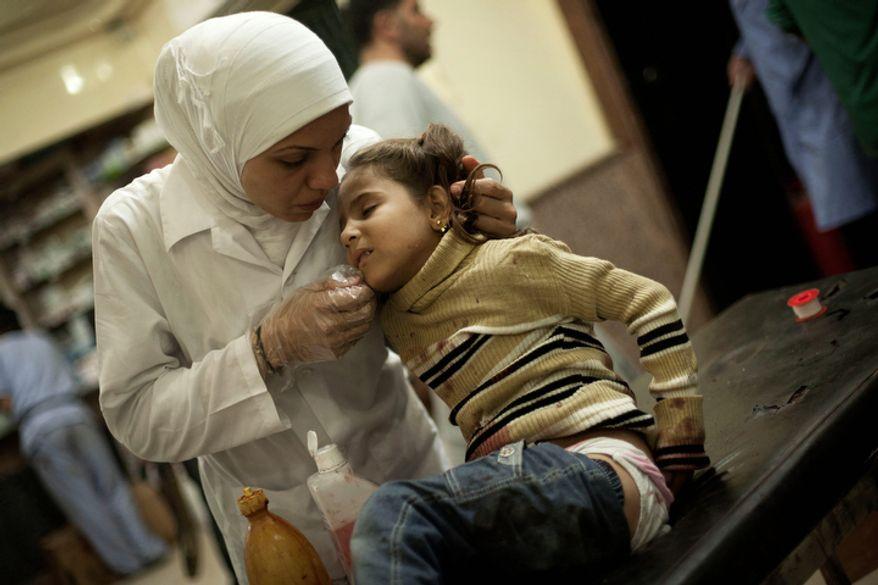 **FILE** A Syrian nurse at Dar al-Shifa hospital in Aleppo, Syria, treats Oct. 10, 2012, a girl wounded by Syrian Army artillery shelling. (Associated Press)