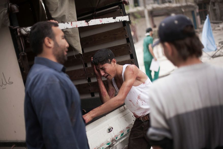 **FILE** A Syrian youth cries Oct. 11, 2012, outside Dar al-Shifa hospital in Aleppo, Syria, while standing next to the truck holding the body his brother, who was killed by Syrian Army shelling. (Associated Press)