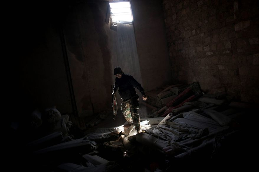 **FILE** A Free Syrian Army fighter stands Oct. 14, 2012, in rubble in a storage room in the Karmal Jabl district of Aleppo, Syria. (Associated Press)