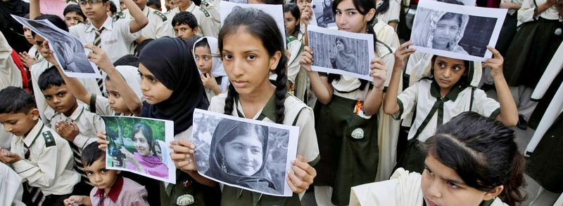 Pakistani students hold pictures of 14-year-old schoolgirl Malala Yousufzai, who was shot by the Taliban, during a protest on Saturday. (Associated Press)