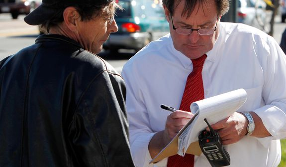 Denver Police Detective Randy Denison, right, takes a statement from Scott Christiansen at Fero's Bar and Grill in Denver on Wednesday, Oct. 17, 2012, where the bodies of a man and four women were discovered after firefighters extinguished a fire at the bar early in the morning. Police think the blaze was set to cover up the slayings. Christiansen says he was a regular customer at the bar. (AP Photo/Ed Andrieski)