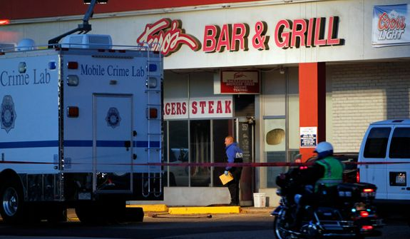 Police are pictured at Fero's Bar and Grill in Denver on Wednesday, Oct. 17, 2012, where the bodies of a man and four woman were discovered after firefighters extinguished a fire at the bar early Wednesday morning. (AP Photo/Ed Andrieski)
