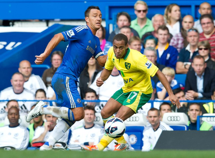 Chelsea's John Terry, left, controls the ball past Norwich City's Elliott Bennett during their English Premier League soccer match at the Stamford Bridge Stadium, London, Saturday, Oct. 6, 2012. (AP Photo/Tom Hevezi)