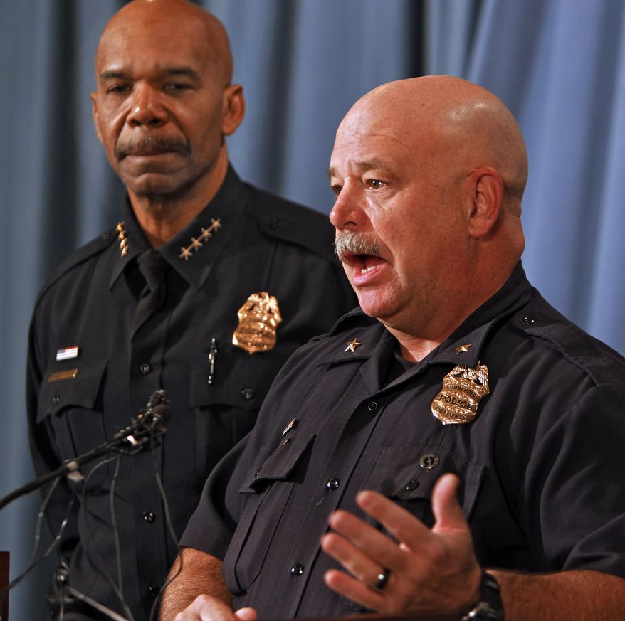 Denver police Cmdr. Ron Saunier (right) speaks at police headquarters on Thursday, Oct. 18, 2012, about the arrest of three suspects in the killing of five people and a fire at a Denver bar. Police Chief Robert White listens at left. (AP Photo/Ed Andrieski)