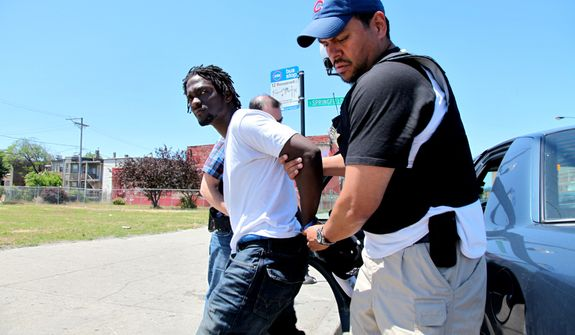 In a June 5, 2012 photo, Devon Wright, 23, is arrested  and charged with delivery of a controlled substance, in Chicago. The Chicago Police Department is waging a strategic battle against gang members and drug dealers. (AP Photo/Robert Ray)