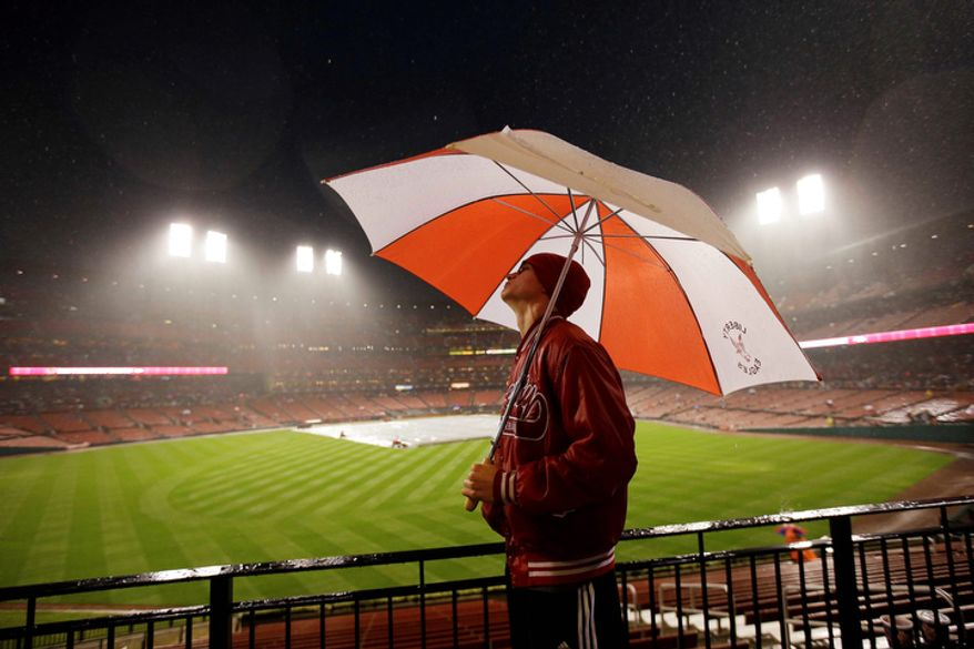 Tyler Ormond from Liberty, Ill., looks at the scoreboard during a rain delay of Game 3 of baseball's National League championship series between the St. Louis Cardinals and the San Francisco Giants, Wednesday, Oct. 17, 2012, in St. Louis. (AP Photo/Mark Humphrey)