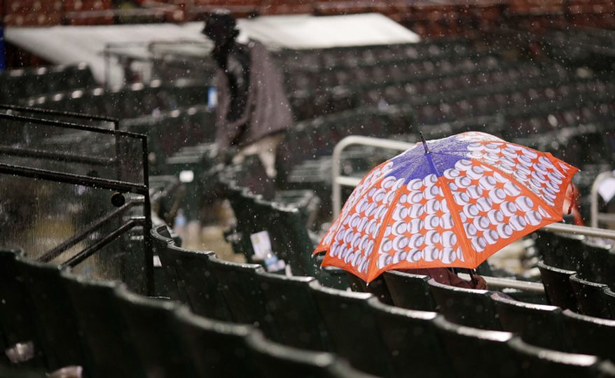 A fan waits out in the stand during a rain delay of Game 3 of baseball's National League championship series between the St. Louis Cardinals and the San Francisco Giants, Wednesday, Oct. 17, 2012, in St. Louis. (AP Photo/Patrick Semansky)