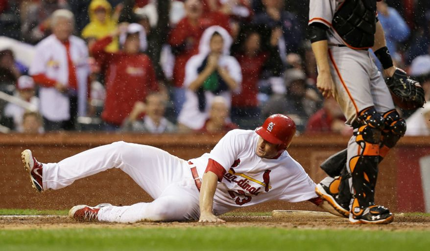 St. Louis Cardinals' David Freese (23) slides to score a run on a hit by Daniel Descalso (33) during the seventh inning of Game 3 of baseball's National League championship series against the San Francisco Giants, Wednesday, Oct. 17, 2012, in St. Louis. (AP Photo/David J. Phillip)
