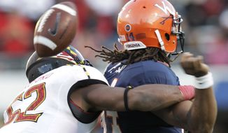 Maryland linebacker Darin Drakeford (52) forces a fumble by Virginia quarterback Phillip Sims during the second half of an NCAA college football game in Charlottesville, Va., Saturday, Oct. 13, 2012. Maryland won 27-20. (AP Photo/Steve Helber)