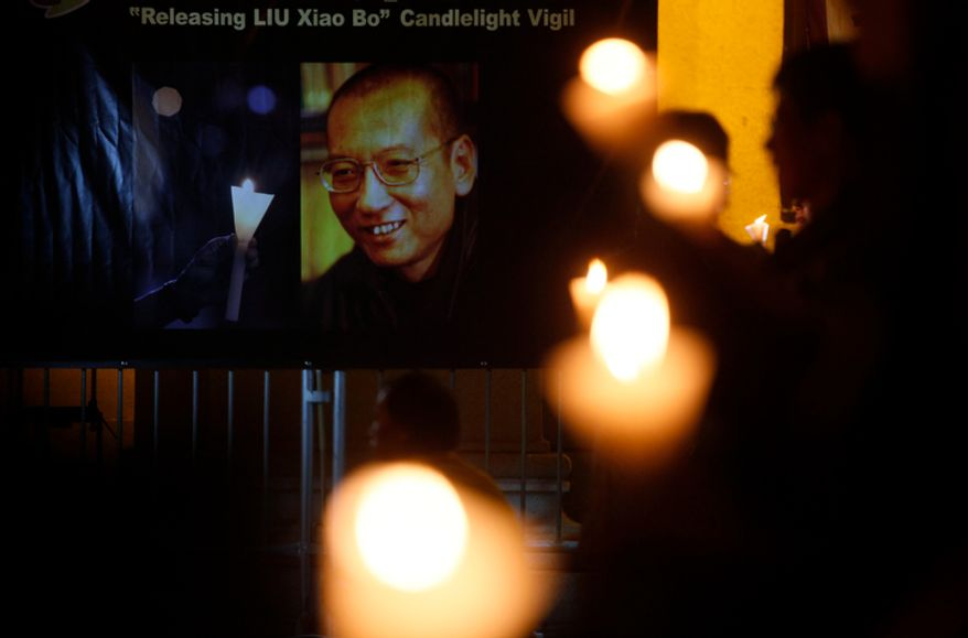 """Pro-democracy protesters display a picture of Chinese dissident Liu Xiaobo with words """"Releasing Liu Xiaobo"""" during a candlelight vigil demonstration in Hong Kong Tuesday, Nov.2, 2010. A human rights watchdog has slammed the U.N. secretary-general for failing to press China's president to release an imprisoned Nobel Peace laureate, accusing Ban Ki-Moon of caring more about his own re-election than the protection of dissidents. (AP Photo/Kin Cheung)"""