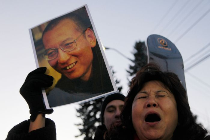"""Protestos scream for the freedom of Nobel peace laureate Liu Xiaobo Thursday Dec. 9, 2010 outside te Chinese Embassy in Oslo, Norway. A day before the Nobel committee honors Liu, an imprisoned Chinese dissident with its peace prize, China ratched up the rhetoric calling the award """"an interference"""" in its internal affairs. (AP Photo/John McConnico)"""