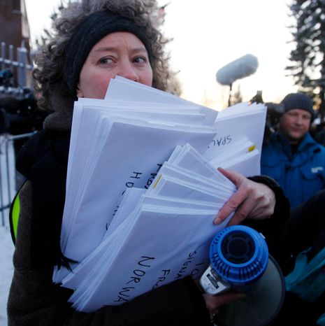 """A representative of Amnesty International holds petitions signed by 100,000 people around the world to demand the freedom of Nobel peace laureate Liu Xiaobo Thursday Dec. 9, 2010 outside te Chinese Embassy in Oslo, Norway. A day before the Nobel committee honors Liu, an imprisoned Chinese dissident with its peace prize, China ratched up the rhetoric calling the award """"an interference"""" in its internal affairs. (AP Photo/John McConnico)"""