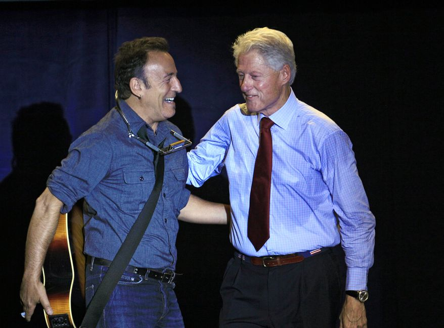 Former President Bill Clinton (right) greets singer-songwriter Bruce Springsteen at a campaign event for President Obama on Thursday, Oct. 18, 2012, in Parma, Ohio. (AP Photo/Tony Dejak)