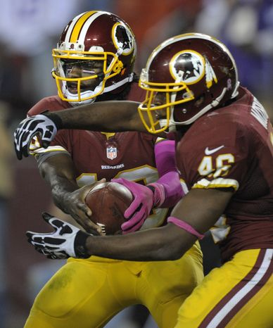 Washington Redskins quarterback Robert Griffin III hands-off the football to running back Alfred Morris during the second half of an NFL football game between the Redskins and Minnesota Vikings Sunday, Oct. 14, 2012, in Landover, Md. The Redskins defeated the Vikings 38-26. (AP Photo/Cliff Owen)