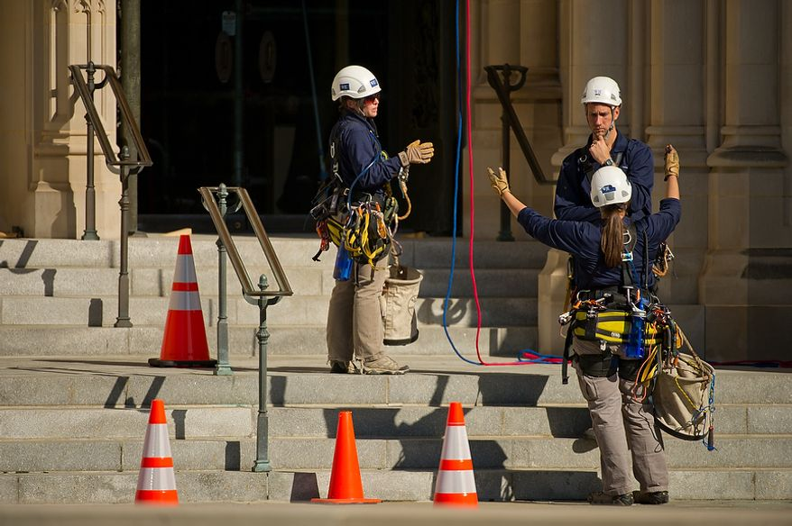 """Difficult Access Team"" engineers Katie Francis, bottom right, and Ema Cardini, left, talk with Team Leader Erik Sohn after they finish repeling down the west front façade of the Washington National Cathedral to check for possible damage from a magnitude 5.8 earthquake that struck the East Coast on August 23, Washington, DC, Monday, October 17,  2011. (Andrew Harnik / The Washington Times)"